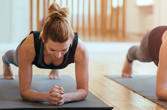 Front view of two sporty fit and slim middle aged women doing planking exercise indoors together with a natural light in modern interior sport studio hall or yoga class.